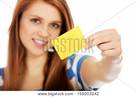 Teenage woman holding empty business card.