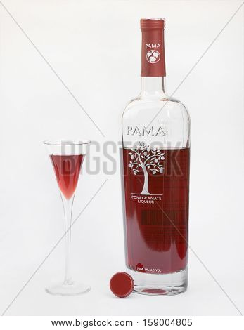 DAYTON, OHIO-NOVEMBER 29, 2016:Bottle of Pama Pomegranate Liqueur sits with cordial filled glass produced by PAMA Spirits Co. Bardstown, Kentucky with ingredients of pomegranate juice, vodka & tequila