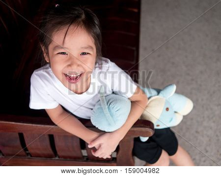 portrait of a little asian kid girl hug her bolster smile face sit down on the wood sofa