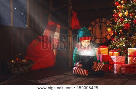 happy child girl elf helper of Santa with a magic Christmas gift