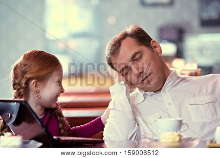 Daughter bothering her father while he resting at cafe