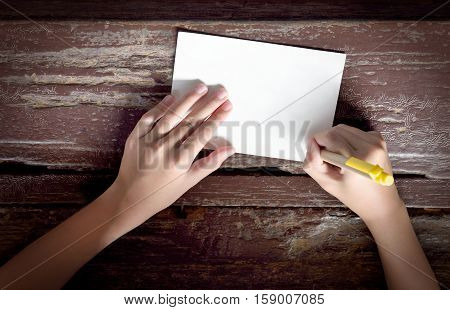 Top view of kid hand with yellow pen writing on paper note or postcard on old wooden table background. Flat lay of child's hands writing or drawing. Blank paper for copy space.