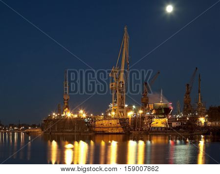 Dry dock in the moonlight at the shipyard in Gdansk Poland.