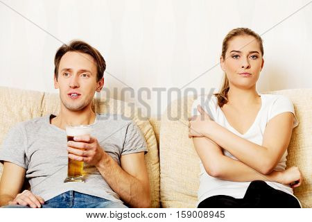 Woman sitting bored while man watching sports