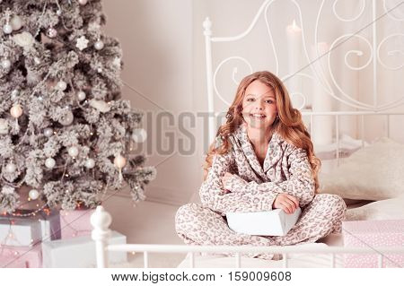 Smiling kid girl 9-10 year old sitting in bed with presents over Christmas tree in room. Christmas morning. Celebration.