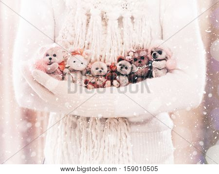 Female hands holding a cute teddy bears. Woman hands in white mittens showing a teddy bears gift dresses in knitted hat and scarf. Cute Christmas present. Winter holidays concept.