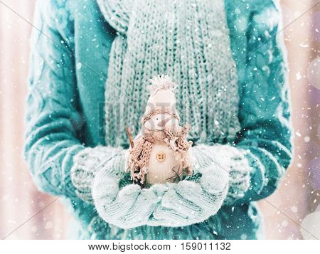 Female hands holding a cute White snowman. Woman hands in teal mittens showing a snowman gift dresses in pink knitted hat and scarf. Cute Christmas present. Winter holidays concept.