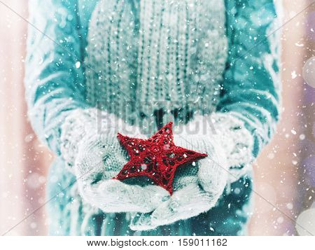 Female hands in light teal knitted mittens with entwined red star on a white snow background. Winter and Christmas cozy concept.