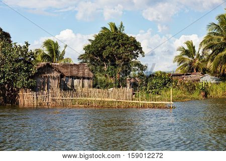 Madagascar traditional rural landscape with fisherman hut in Tamatave province near Maroantsetra city. Countriside wilderness virgin natural scene in North eastern Madagascar poster