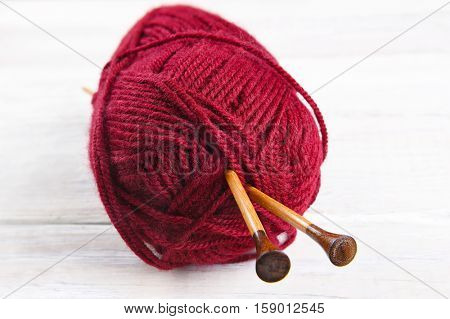 A skein of red yarn with wood knitting needles. Closeup in horizontal format