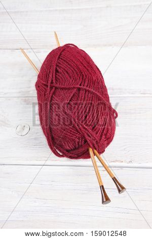 A skein of red yarn with wood knitting needles. Vertical format from a high angle.