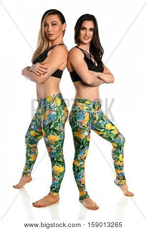 Two young women in exercise attire isolated over white background