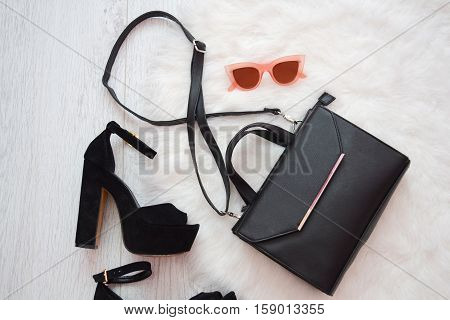 Fashion concept. Black handbag shoes and pink glasses on a white background. top view