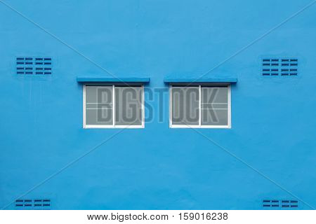 Two sliding glass window on the blue wall.