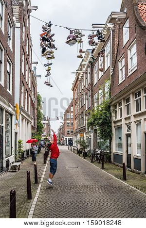 Amsterdam Netherlands - August 2 2016: Girl jumping trying to reach hanging shoes in a street in historical city center of Amsterdam.