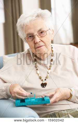 Senior Woman Sorting Medication Using Organiser At Home