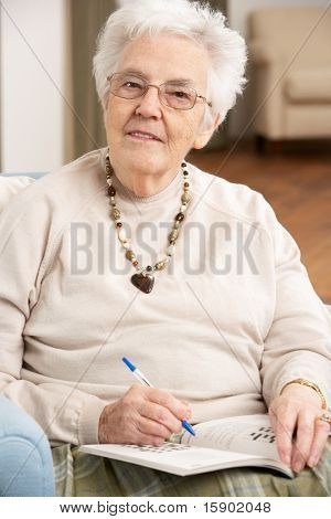 Senior Woman Relaxing In Chair At Home Completing Crossword