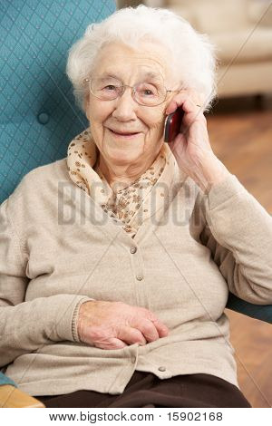 Senior Woman Talking On Mobile Phone Sitting In Chair At Home