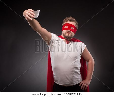 Egoist. Self. Hero. Super Hero. Handsome super hero man making photos on his mobile or smart phone isolated on black in studio.