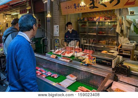 TOKYO, JAPAN - 18 NOV 2016 - Customer shopping fresh seafood in Tsukiji Fish Market, Tokyo, Japan on November 18, 2016.