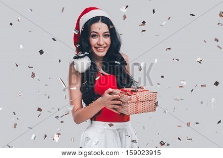 Merry Christmas! Attractive young woman in Santa hat holding gift box and smiling while standing in front of grey background with confetti all around her