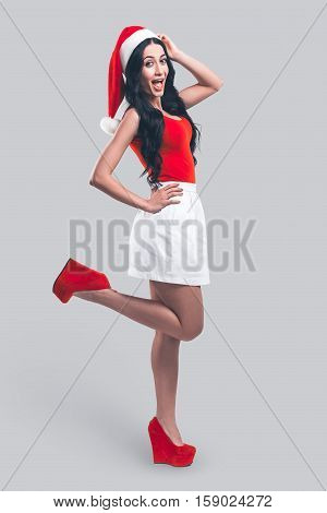 Beauty in Santa hat. Full length of attractive young woman in Santa hat looking at camera and expressing positivity while standing in front of grey background