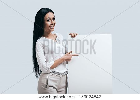 Place new ideas here! Young confident woman in white shirt pointing on blank flipchart while standing against grey background