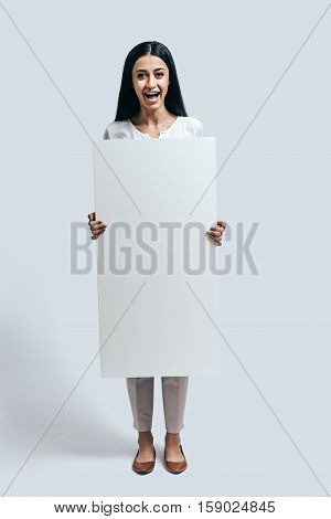 Feeling excited. Full length of young confident woman holding blank flipchart while standing against grey background
