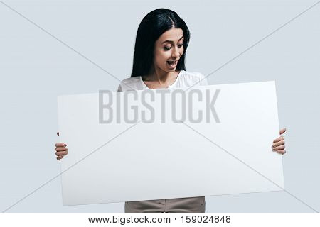 Unexpected surprise. Young confident woman holding blank flipchart with surprised face while standing against grey background