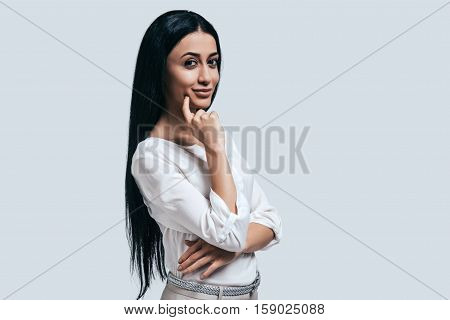 Thinking about new business aproaches. Confident young woman in white shirt smiling and looking at camera while standing against grey background