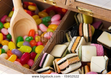 Wooden candy bar with assortment sweets isolated over white