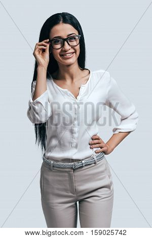Young and confident. Young attractive woman in white shirt and glasses smiling while standing against grey background
