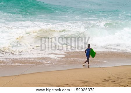 Little boy surfer with a board running along the ocean.