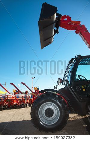 Excavator with bucket and sowing machinery on the background.