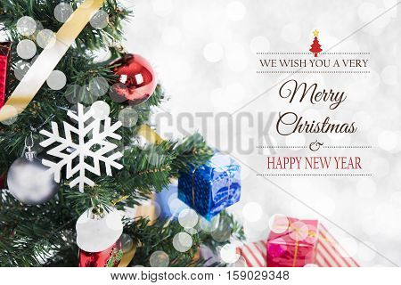 Christmas decorative with gift box and snowflake on christmas tree and Merry Christmas and Happy New Year 2017 text on bokeh light background.