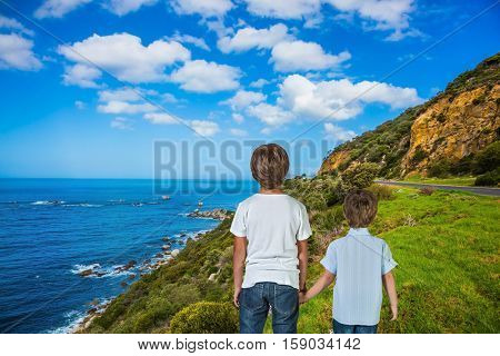 The concept of active tourism and recreation. Two boys standing  on Cape of Good Hope - the south-western point of Africa. Travel to South Africa
