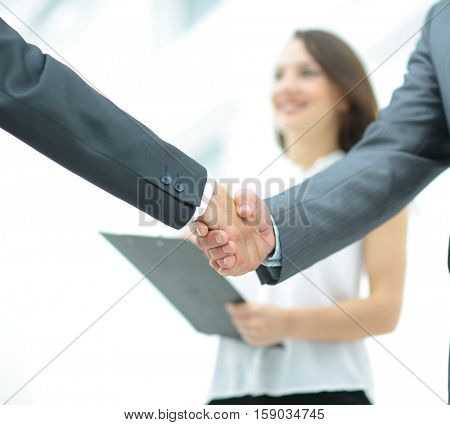 handshake of two businessmen in the background of the experts do