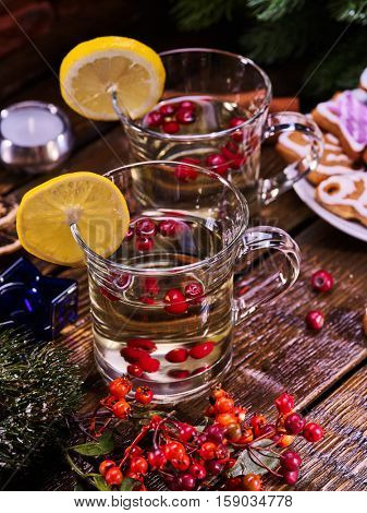 Christmas still life with pair mug decoration lemon slice hot drink on wooden table and gingerbread Cookie. Red berries on foreground. Vertical shot.