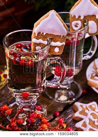 Top of two glass latte mug hot drink. Warming mulled wine with cookie in form of house and red berry.