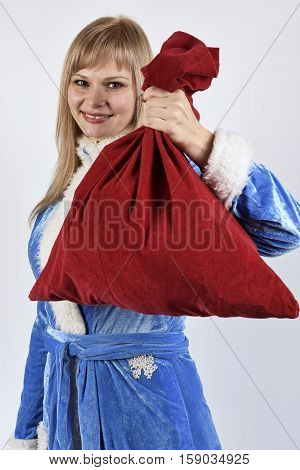 smiling snow maiden posing with bag of toys in hand