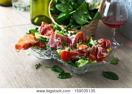 Salad From Jamon , Arugula And Tomatoes On A Kitchen Table
