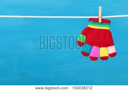 Multicolor striped glove hanging on the clothesline on blue wooden background