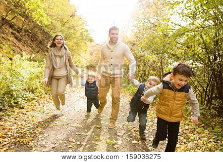 Beautiful young family on a walk in forest, running. Mother and father with their three sons in warm clothes outside in colorful autumn nature.