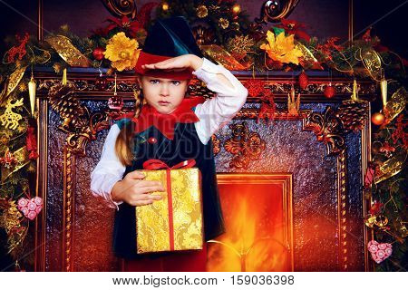 Santa Claus's helpers. Pretty small girl in christmas elf costume in a room beautifully decorated for Christmas. Time of miracles. Gifts from Santa Claus.