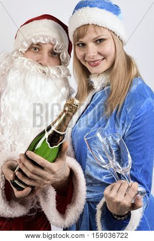 Santa Claus and snow maiden holding a bottle of champagne with glasses