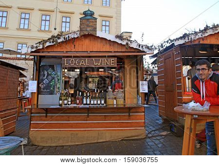 PRAGUE, CZECH REPUBLIC - SEPTEMBER 28, 2015: Local people and tourists eating near wooden stalls with local wine and traditional street food in Prague Castle (Hradcany), Prague, Czech Republic.