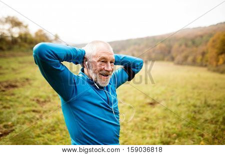 Senior runner in sunny autumn nature doing stretching. Man with earphones, listening music, armband on his arm. Rear view.