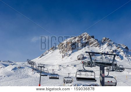 Ski lift in mountains at winter. Alpine winter mountain landscape. French Alps covered with snow in sunny day. Val-d'Isere, Alps, France