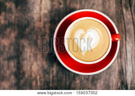 Red cup of cappucino with beautiful latte art on old wooden background. Top View.