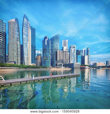 Singapore central quay with water on foreground. Modern city architecture at sunny day
